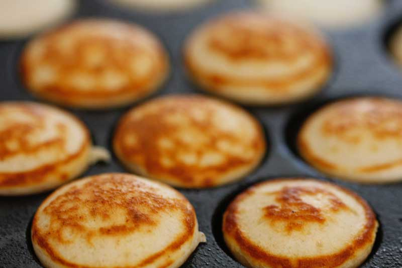 Flip mini dutch pancakes to bake other side using a bamboo skewer